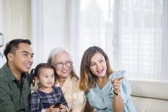 Drie Aziatische generatiefamilie die op TV thuis letten stock afbeelding