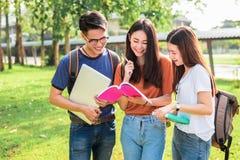 Drie Aziatische jonge campusstudenten genieten tutoring en lezings van boe-geroep stock fotografie