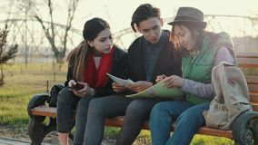 Drie Aziatische tieners die thuiswerk doen bij het park in de zonsondergangtijd stock video