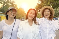 Drie Aziatische vrouwenontspanning openlucht met gelukgezicht stock foto's