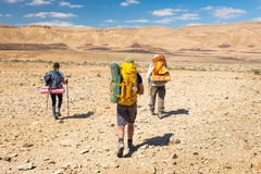 Drie backpackers die de sleep van de steenwoestijn lopen Stock Foto