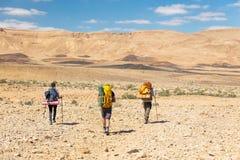 Drie backpackers die de sleep van de steenwoestijn lopen Royalty-vrije Stock Foto