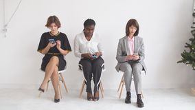 Drie bedrijfsmeisjes verwachten gesprekken zittend op stoelen in de gang van een bureaugebouw stock video