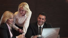 Drie bedrijfsmensen bespreken actief wat zij in hun laptop zien stock video