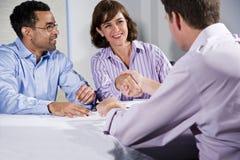 Drie bedrijfsmensen die, mensen die handen schudden samenkomen Stock Afbeelding