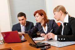 Drie bedrijfsmensen komen samen Stock Foto