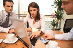 Drie bedrijfspersonen die samen met laptop in zonnig bureau werken Royalty-vrije Stock Afbeelding