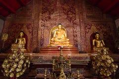 Drie beelden die van Boedha binnen Wat Phra Singh, Thailand zitten Stock Foto