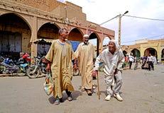 Drie bejaarde Berber-mensen gaan naar souk van de stad van Rissani in Marokko stock foto's