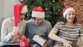 Drie beste vrienden die pret hebben, het houden stelt en het zitten dichtbij Kerstboom voor Close-up stock footage