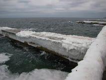 Drie bevroren pijlers aan wal overzees in de winter stock foto