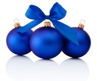 Drie Blauwe die Kerstmisballen met lintboog op wit wordt geïsoleerd Royalty-vrije Stock Afbeeldingen