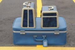 Drie blauwe koffers op gele lijnen Royalty-vrije Stock Afbeeldingen