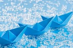 Drie blauwe Origamidocument schepen op blauw water zoals achtergrond stock afbeeldingen