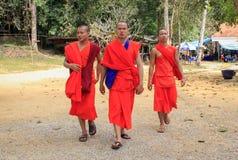 drie boeddhistische monniken in rode robes op aardachtergrond stock afbeelding