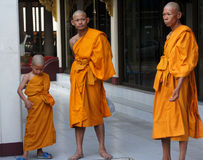 Drie boeddhistische monniken van diverse leeftijden wachten Royalty-vrije Stock Afbeelding