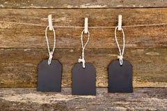 Drie bordmarkeringen met koord het hangen tegen rustiek hout Royalty-vrije Stock Fotografie
