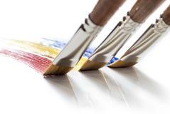 Drie borstels die kleuren schilderen Stock Afbeeldingen
