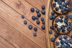 Drie bosbessentartlet op een houten plaat op de lijst, bosbes gebakken shells, fruit cupcake met bosbes stock fotografie