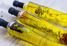 Drie bottes van olijfolie met spieces, rozemarijn, peper, orega Stock Afbeeldingen