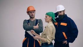 Drie bouwers bespreken het bouwplan Concept bouwwerkzaamheden De vrouw en twee mannen in helmen zijn stock video