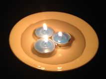 Drie brandende blauwe kaarsen in een plaat met water in dark Ea stock afbeelding