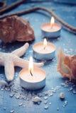 Drie brandende kaarsen op een rij op achtergrond van overzeese voorwerpen, tin Royalty-vrije Stock Afbeelding