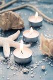 Drie brandende kaarsen op een rij op achtergrond van overzeese voorwerpen, tin Stock Fotografie