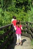 Drie broers die onderaan de loopbrug in het midden van pon lopen Stock Afbeelding