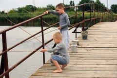 Drie broers kwamen aan de brug in het dorp over de rivier vissen Stock Afbeeldingen