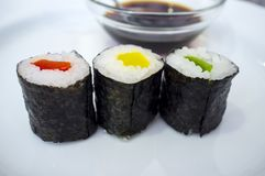 Drie broodjes van pepermakizushi met erachter de kom van de sojasaus Royalty-vrije Stock Foto