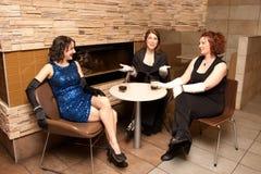 Drie buitensporige vrouwen hebben dranken royalty-vrije stock afbeeldingen