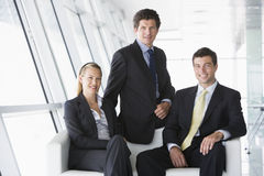 Drie businesspeoplezitting in bureauhal Royalty-vrije Stock Foto's