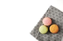 Drie cakes van Frankrijk op grijze keukenhanddoek Handdoek met ornamentlijnen, dozen Makarons op lijst Groene, roze en oranje sno Royalty-vrije Stock Fotografie