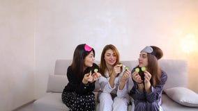 Drie charmante vrouwelijke vrienden ontspannen en maken gezichtsschoonheidsbehandelingen in slaapkamer in avond stock videobeelden