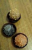 Drie chocolade in document manden op een houten lijst Close-up royalty-vrije stock foto's