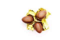 Drie chocoladeeieren op een gouden folie Stock Afbeeldingen