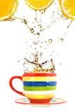 Drie citroenen, kleurenkop en plons van thee Royalty-vrije Stock Afbeeldingen