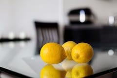 Drie citroenen op de glaslijst Stock Afbeelding