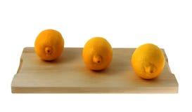 Drie citroenen op een hakbord stock foto's