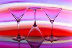 Drie cocktail/martini-glazen op een rij met een regenboog van kleur achter hen royalty-vrije stock fotografie