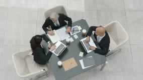 Drie collectieve bedrijfsmensen die in bureau samenkomen die laptop computers met behulp van stock videobeelden