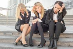 Drie collectieve bedrijfsvrouwen die op treden zitten Stock Foto's