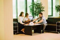 Drie collega's die de toekomstige werkzaamheden van het businessplan bespreken Stock Fotografie