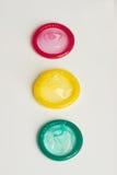 Drie condomen worden geplaatst die als Stock Fotografie