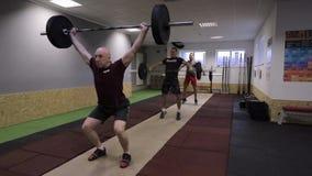 Drie CrossFit-atleten die Schone - en uitvoeren - schokoefening stock footage