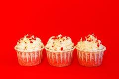 Drie cupcakes met gevoelige witte room op een rode achtergrond royalty-vrije stock afbeelding