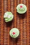 Drie cupcakes op een mand Stock Afbeeldingen