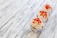 Drie cupcakes op een oude witte uitstekende achtergrond op de raad royalty-vrije stock afbeeldingen