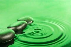 Drie dalingen van de kuuroordsteen liggen in het groene water Stock Afbeelding